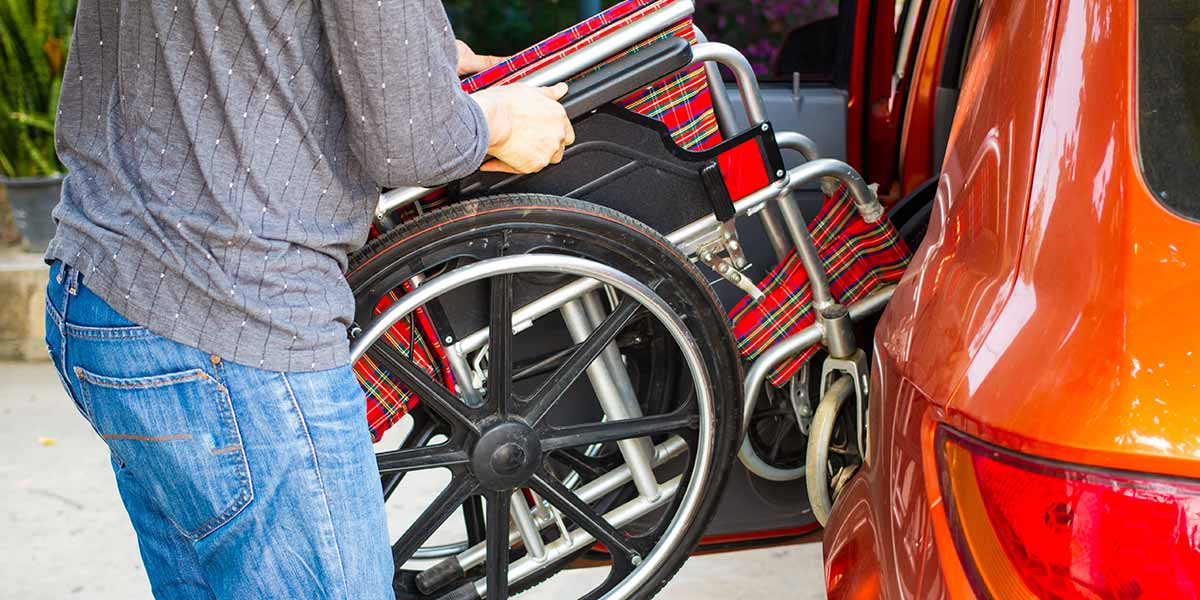 Man folding wheelchair in a car