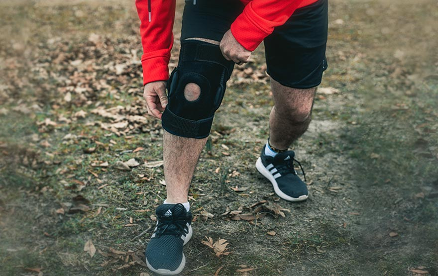 Man holding knee brace