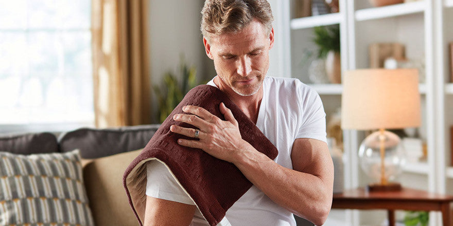 Man using heating pad on a sore shoulder