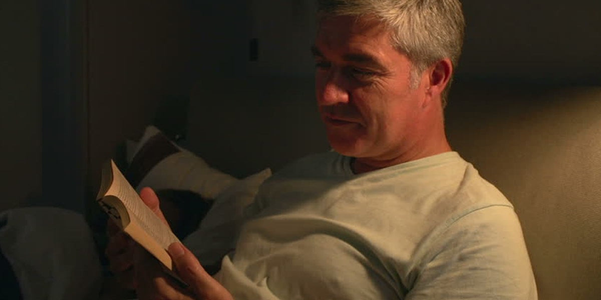 Old man reading a book before sleeping