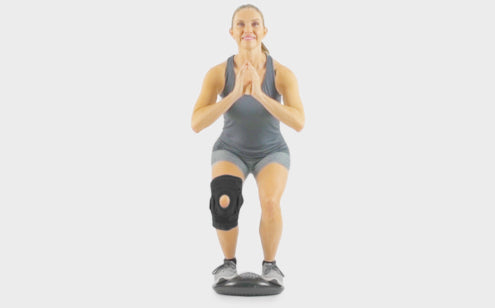 Middle age woman with hinged knee brace excercising