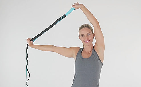 woman stretching arms overhead with stretch strap