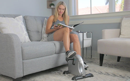 Middle age woman using pedal exerciser while reading magazine