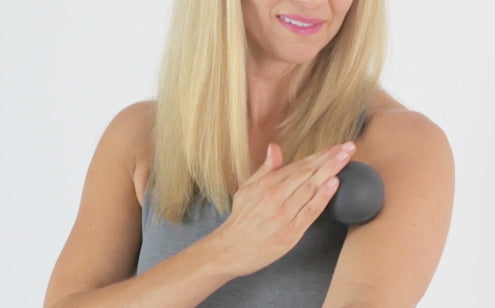 Woman using massage ball to massage her shoulder