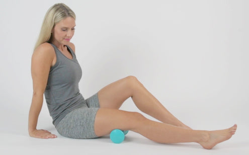 Middle age woman massaging her thigh with massage ball