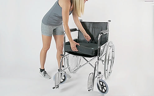 Woman placing cushion in a wheel chair