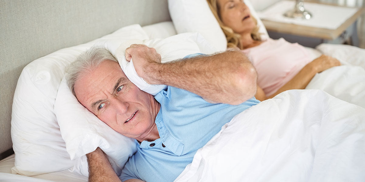 Senior man lying on bed and covering his ears with pillow in bedroom
