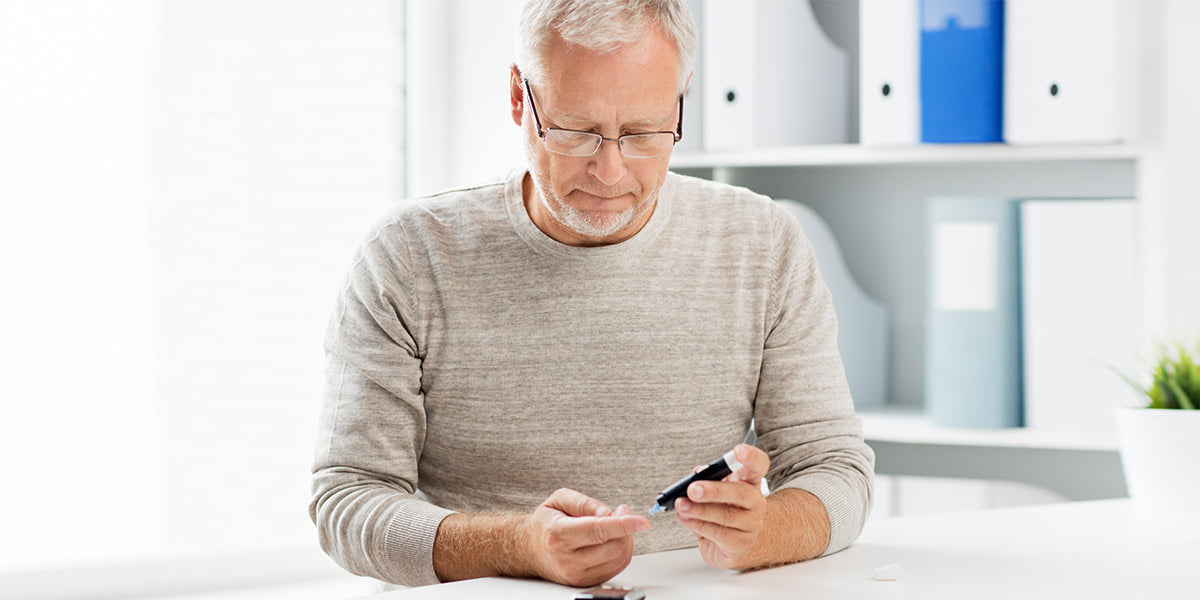 Senior man with glucometer checking blood sugar level at home