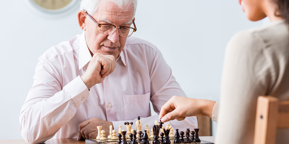 Senior smart man playing chess with young happy caregiver
