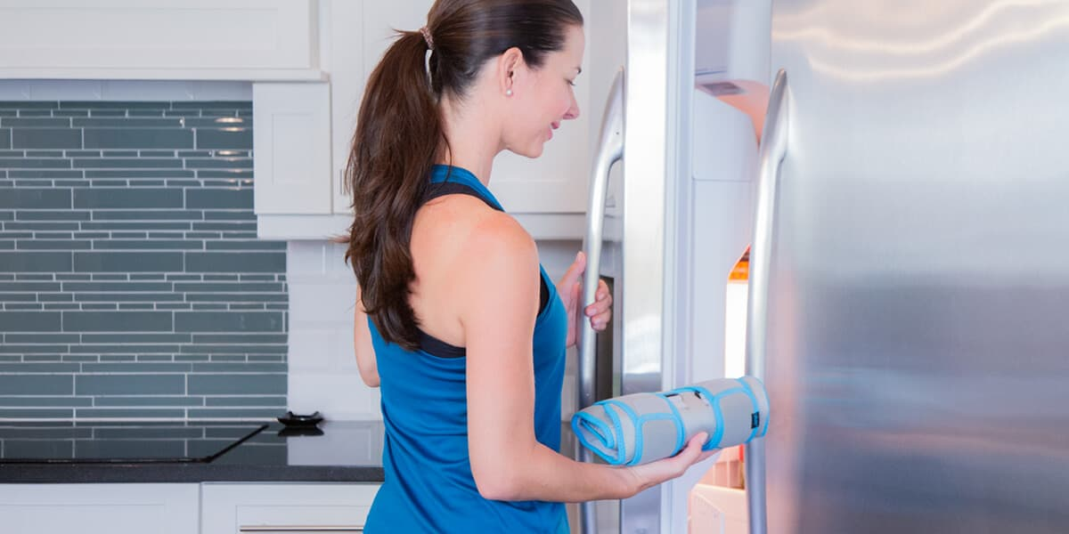 Woman placing cold wrap in freezer