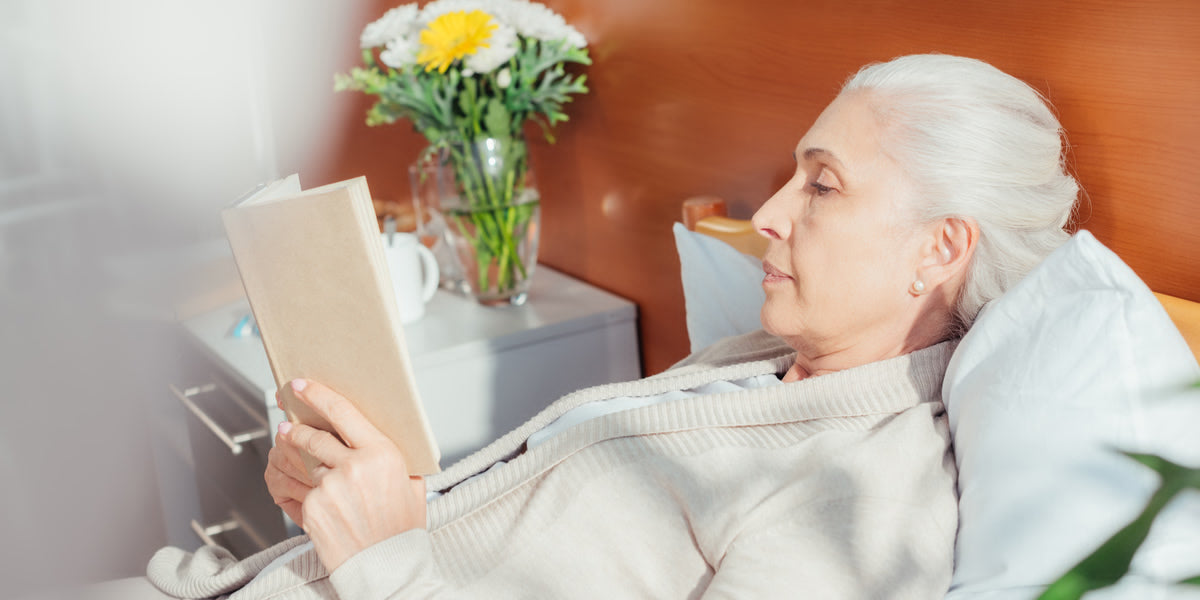 Side view of senior woman reading book in hospital