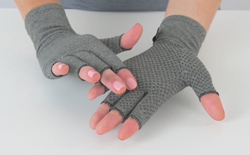Hand wearing arthritis gloves with grips touching the texture