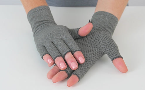 Hand wearing arthritis gloves with grips
