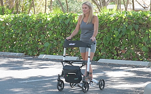 Middle age woman using a rollator with bag