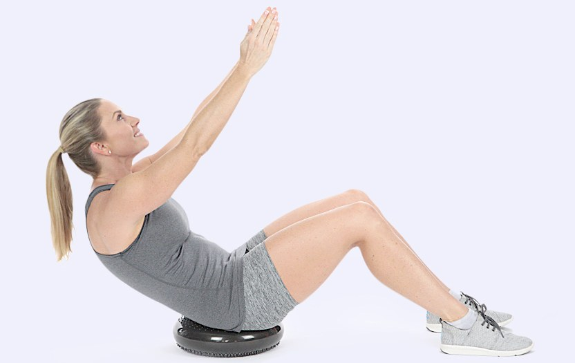Woman doing a stretching pose on a wobble cushion