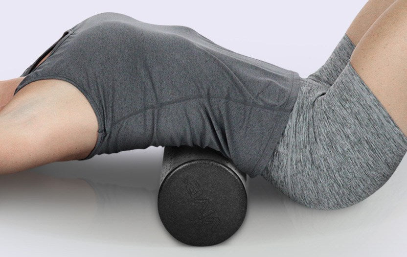 Woman using foam roller on her lower back