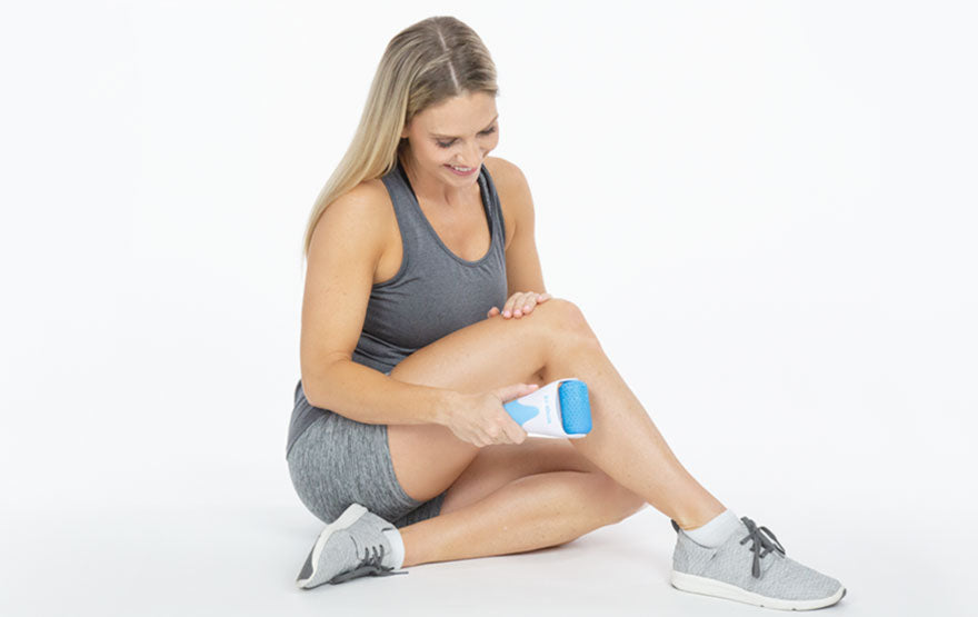 Woman using cold roller on shin