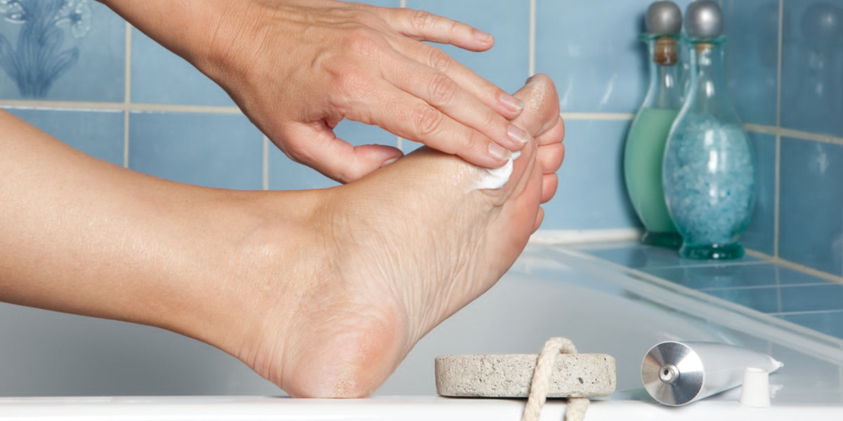 Woman's hands putting cream on callous feet