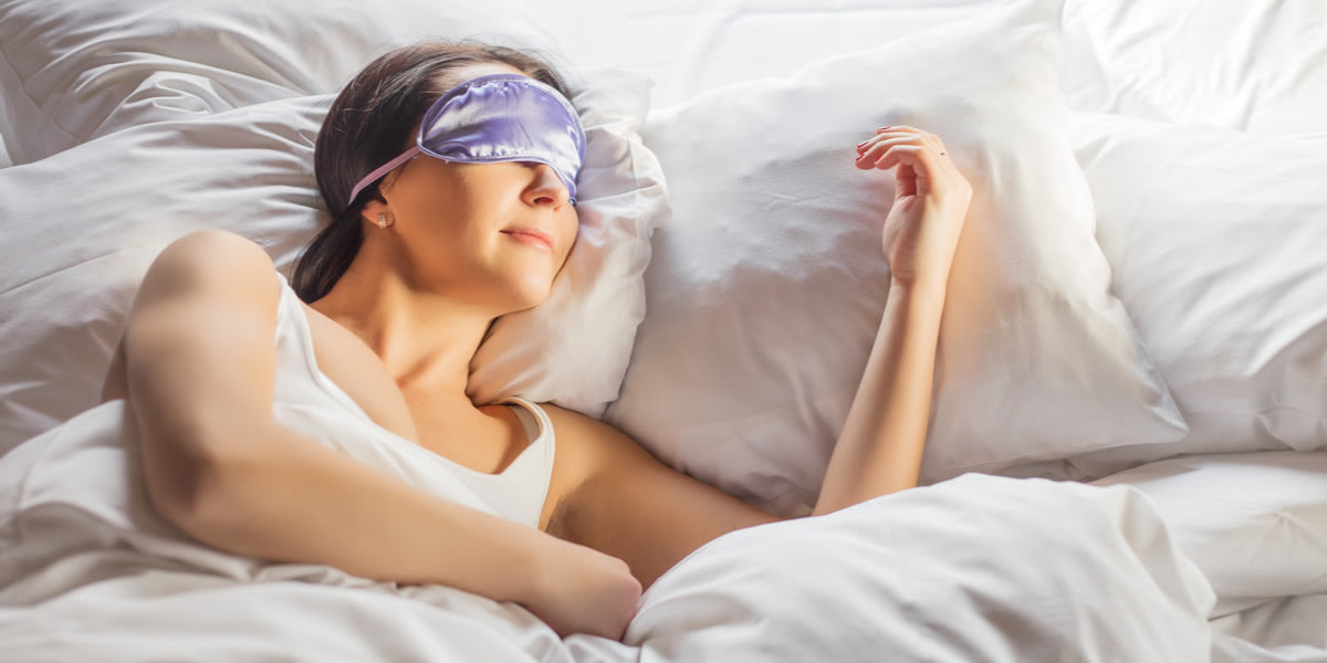 Woman sleeping in bed with en eye mask