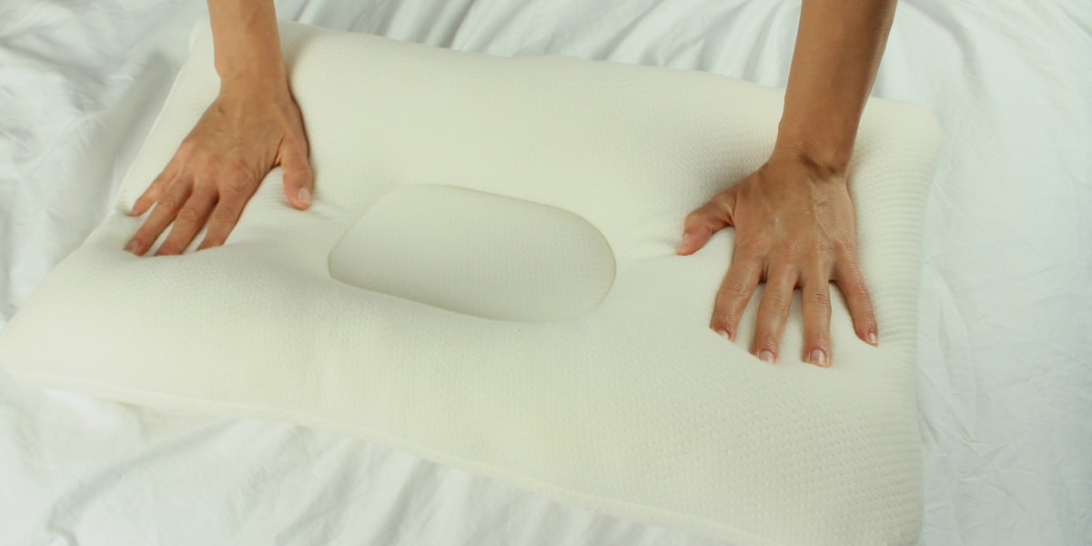 hand pressing down to check firmness of pillow