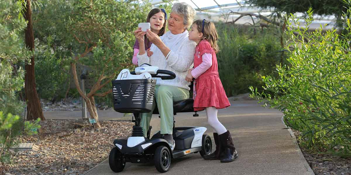 elderly woman in a mobility scooter with two kids