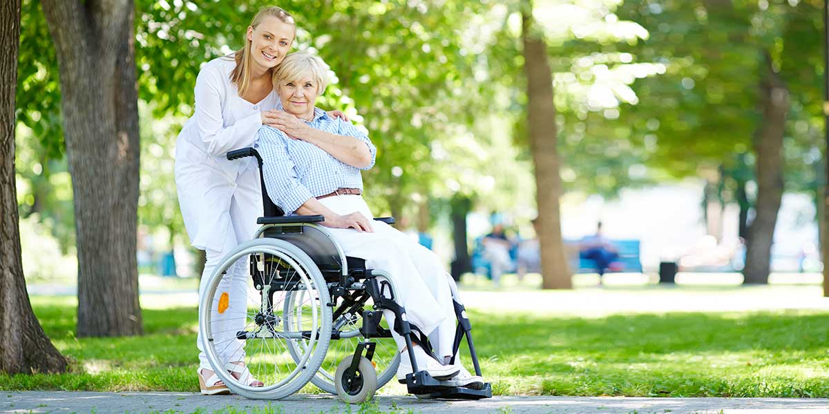 elderly woman in wheelchair with a nurse