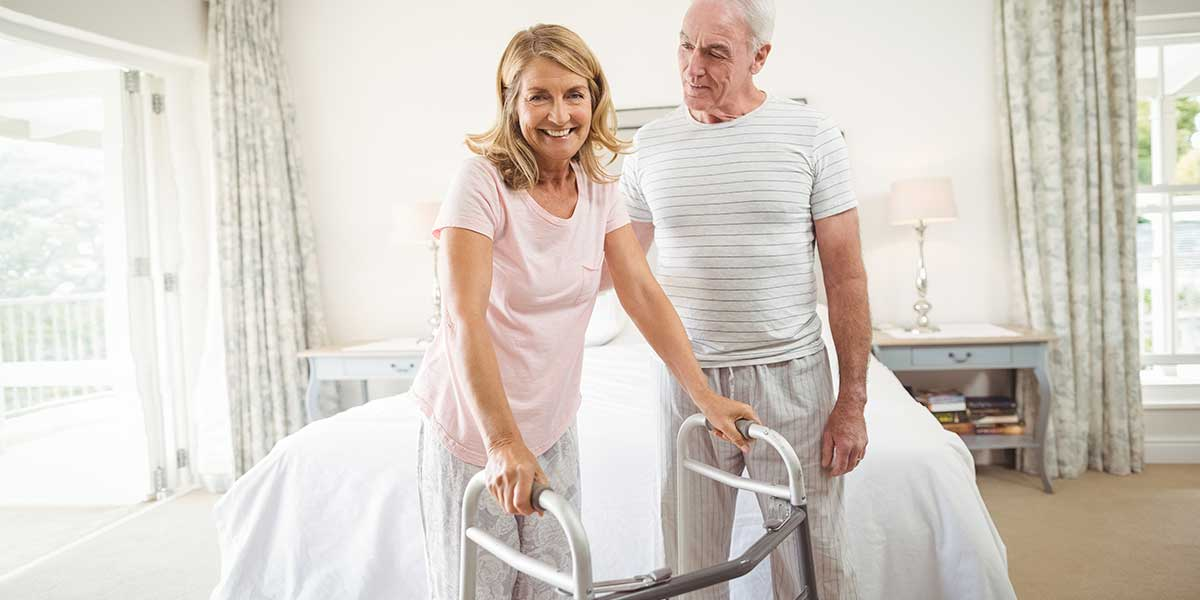 elderly woman using a walker assisted by her husband