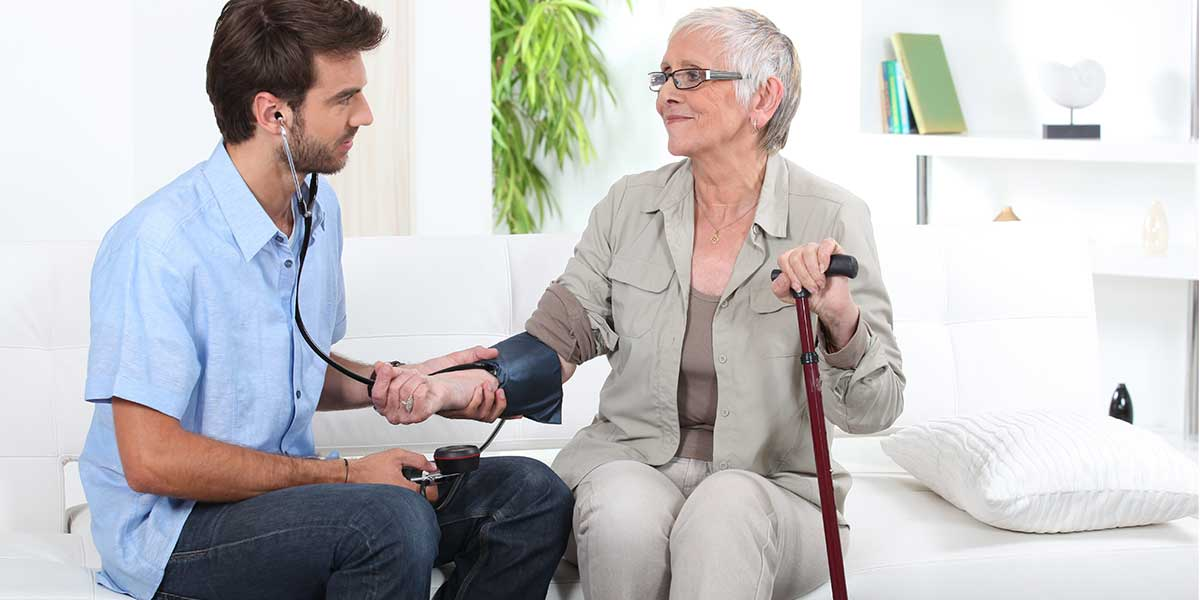 man checking blood pressure of a senior woman
