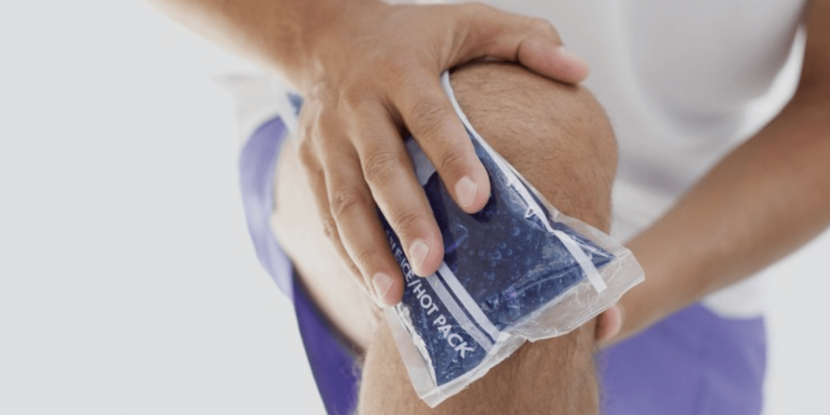 man putting ice pack on knee