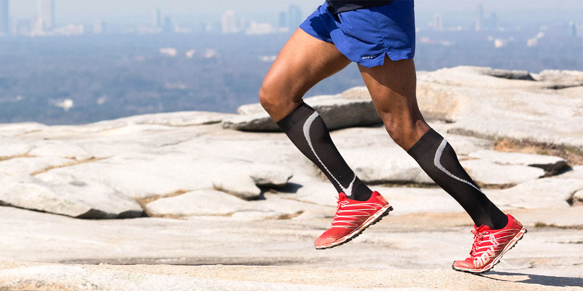 man running wearing compression leg sleeves