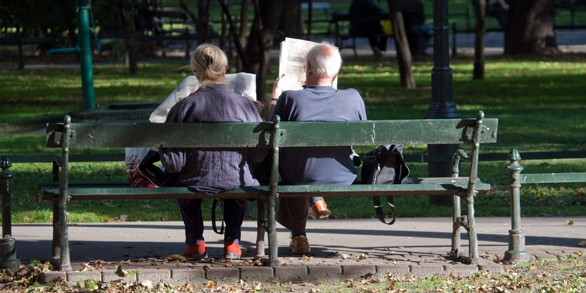 couple reading the newspaper on bench