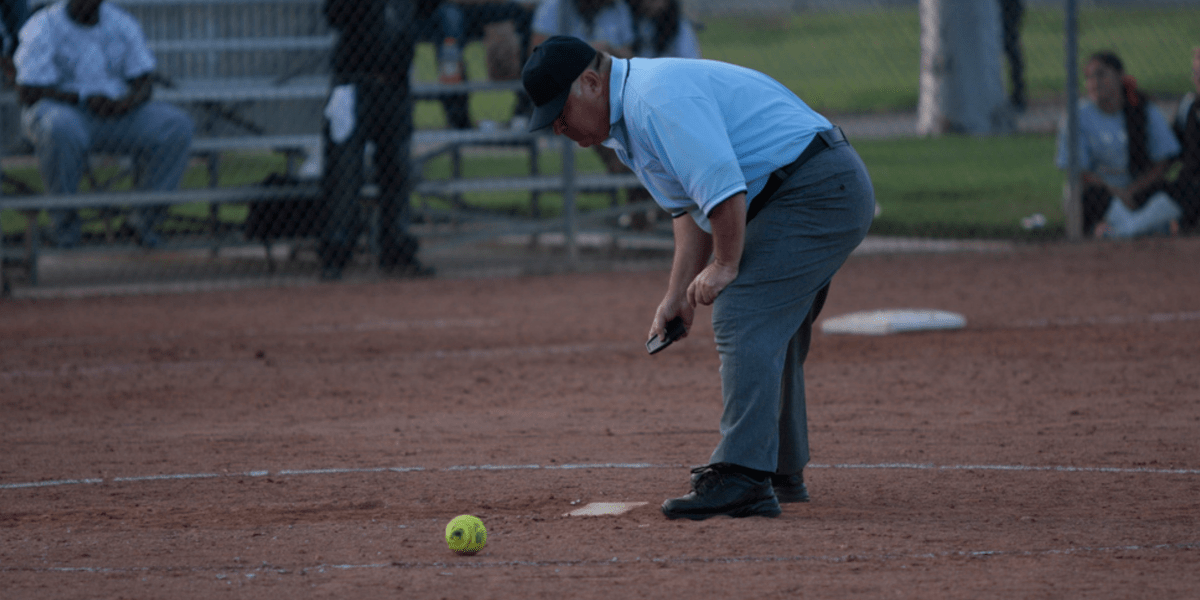 softball umpire brushing base