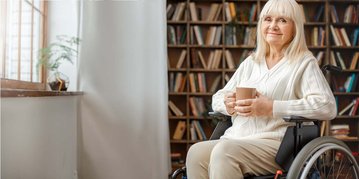 woman sitting on a wheelchair holding a mug