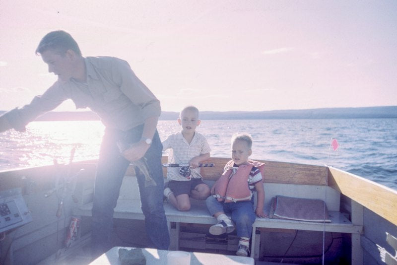 A father on a fishing boat with his two children