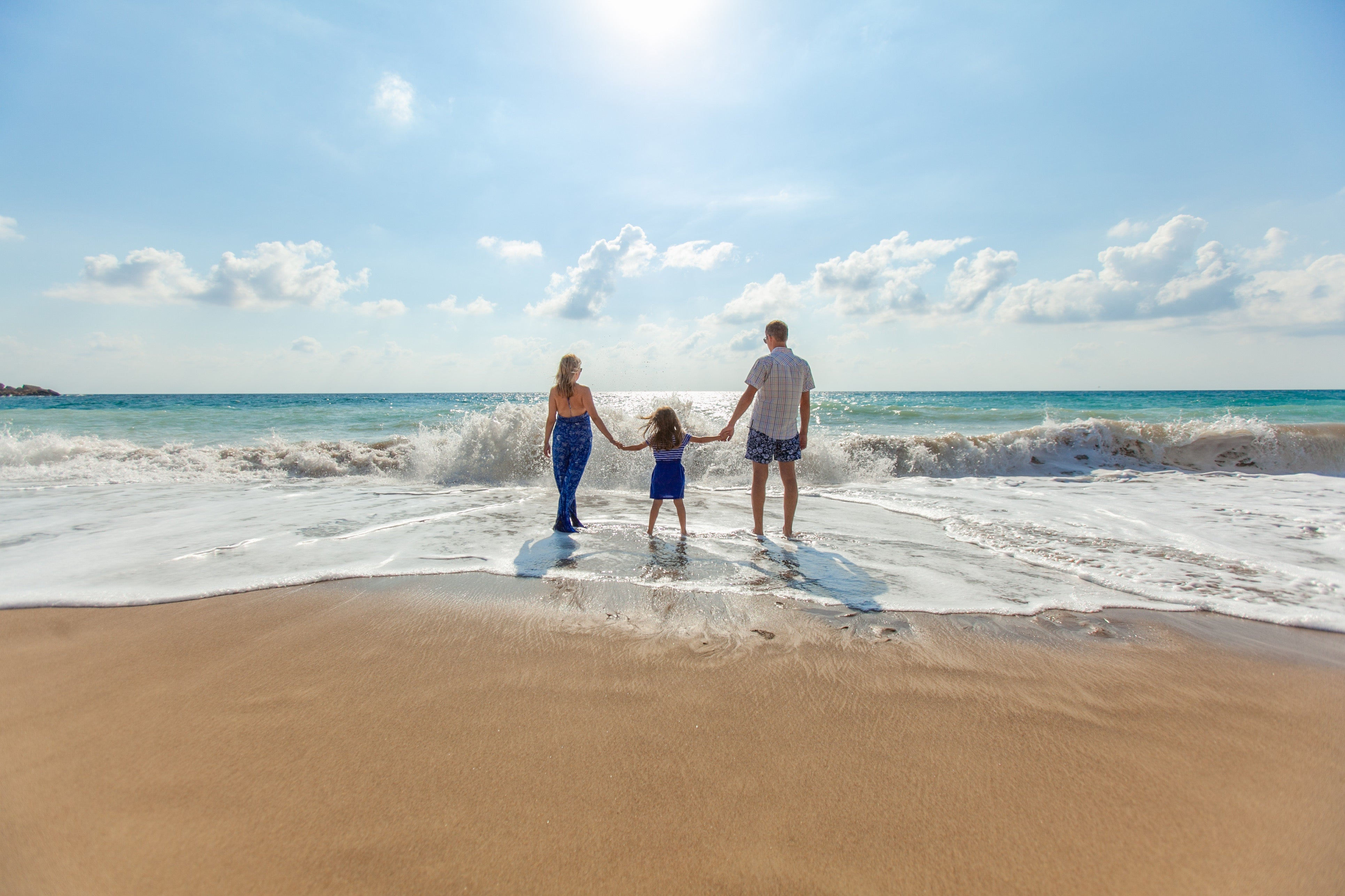 Family of three enjoying the sun, sand and waves