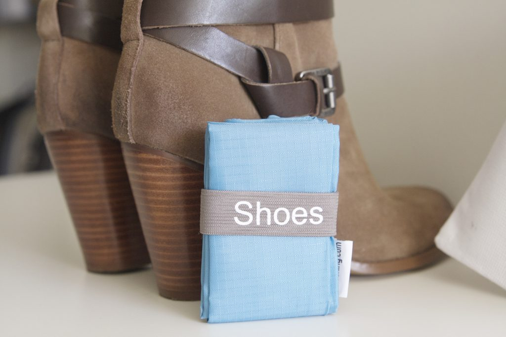A pair of boots and folded travel shoe bag