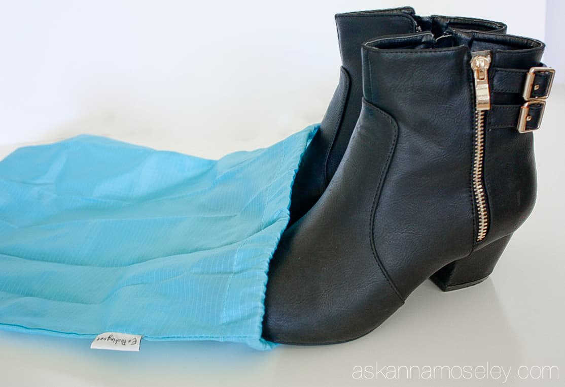 A pair of boots in a travel shoe bag