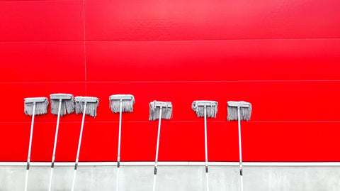A row of mops propped on a bright red wall