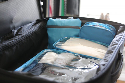 An organized suitcase with turquoise clear packing cubes