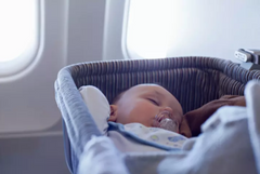 Baby sleeping on airplane bassinet, an essential tip for making a flight easier for infants
