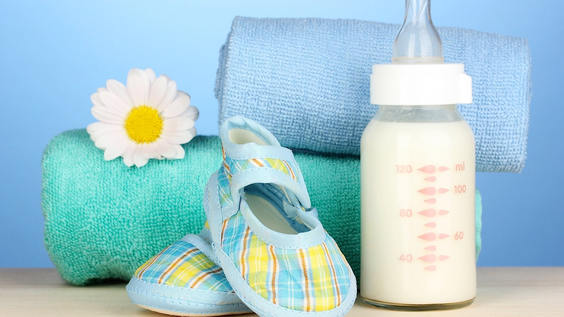 Cute baby shoes and bottled milk with pastel-colored towels on background