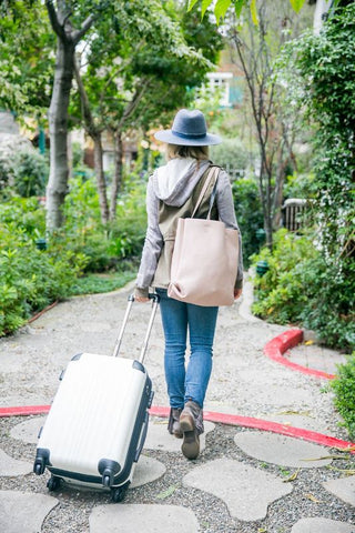 Blonde girl wearing hat carrying suitcase for honeymoon trip