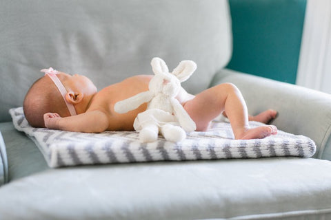Infant laying on blanket propped on couch