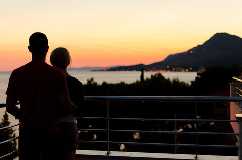 Couple watching sunset while on honeymoon