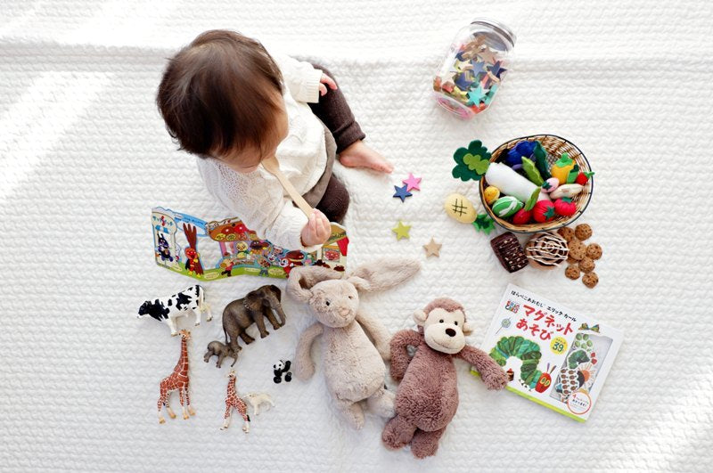 Cute toddler on flight playing with stuffed animals, vegetable toys and animal figures