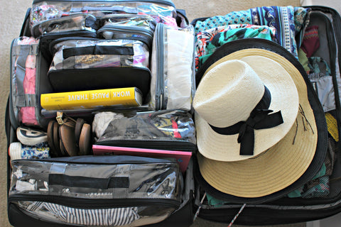 Clear packing cubes inside suitcase along with hats, books and shoes
