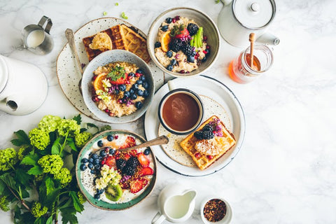 Flatlay of a healthy, well-planned breakfast of fruits, grain, waffles, and honey