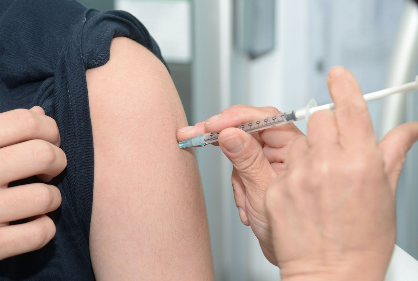 Woman getting flu vaccine before traveling