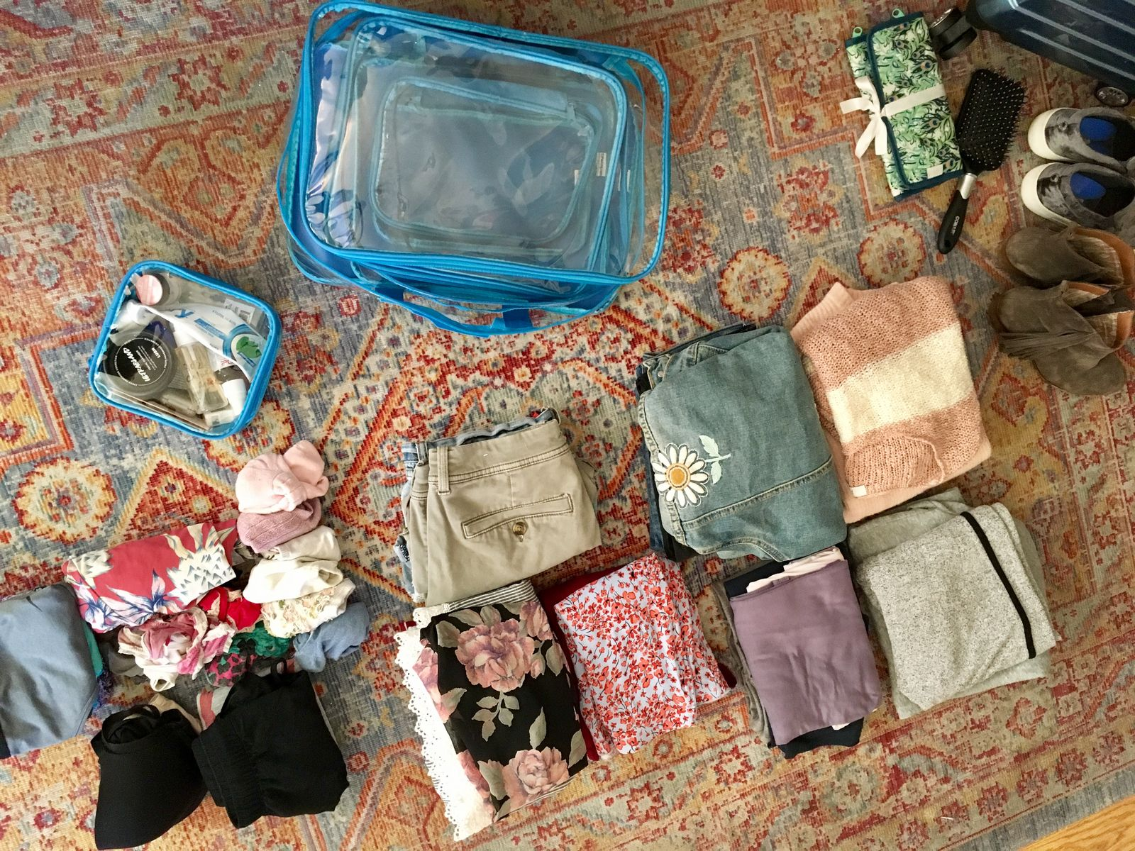 Folded clothes and packing cubes on the floor
