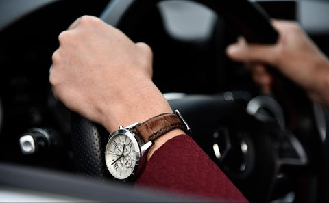 Man wearing watch driving car